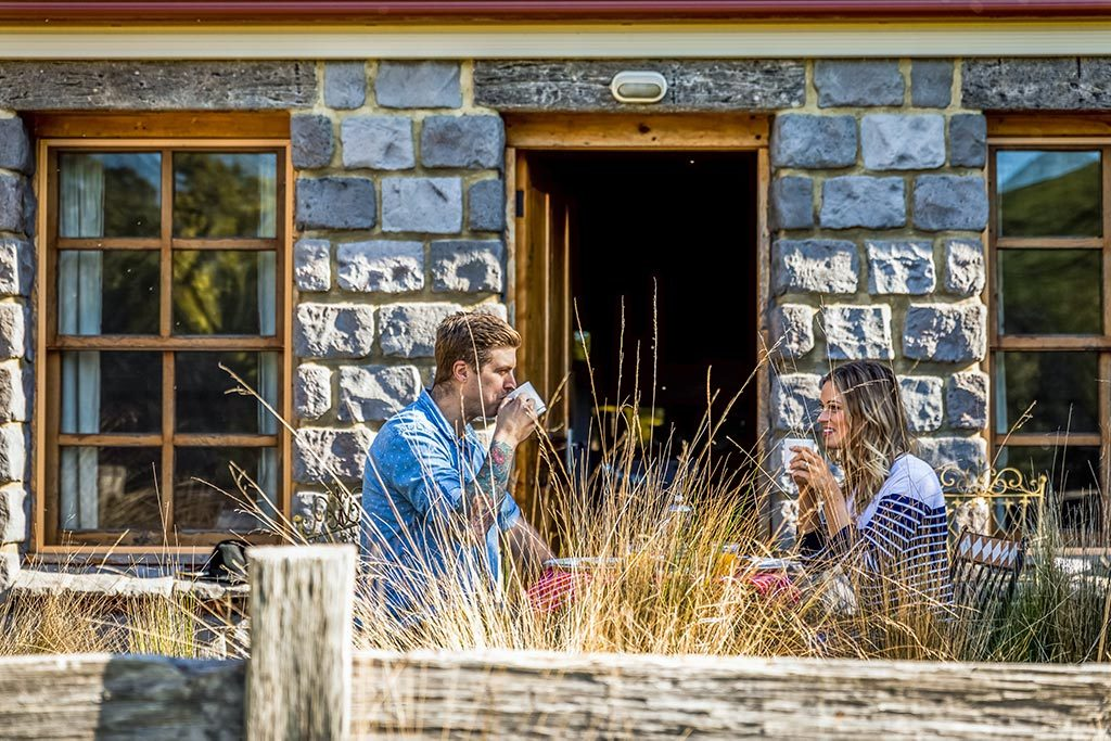 A young couple sitting outside the stone cottage having their breakfast