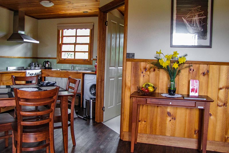 Cottage interior showing kitchen area and entrance to the bathroom
