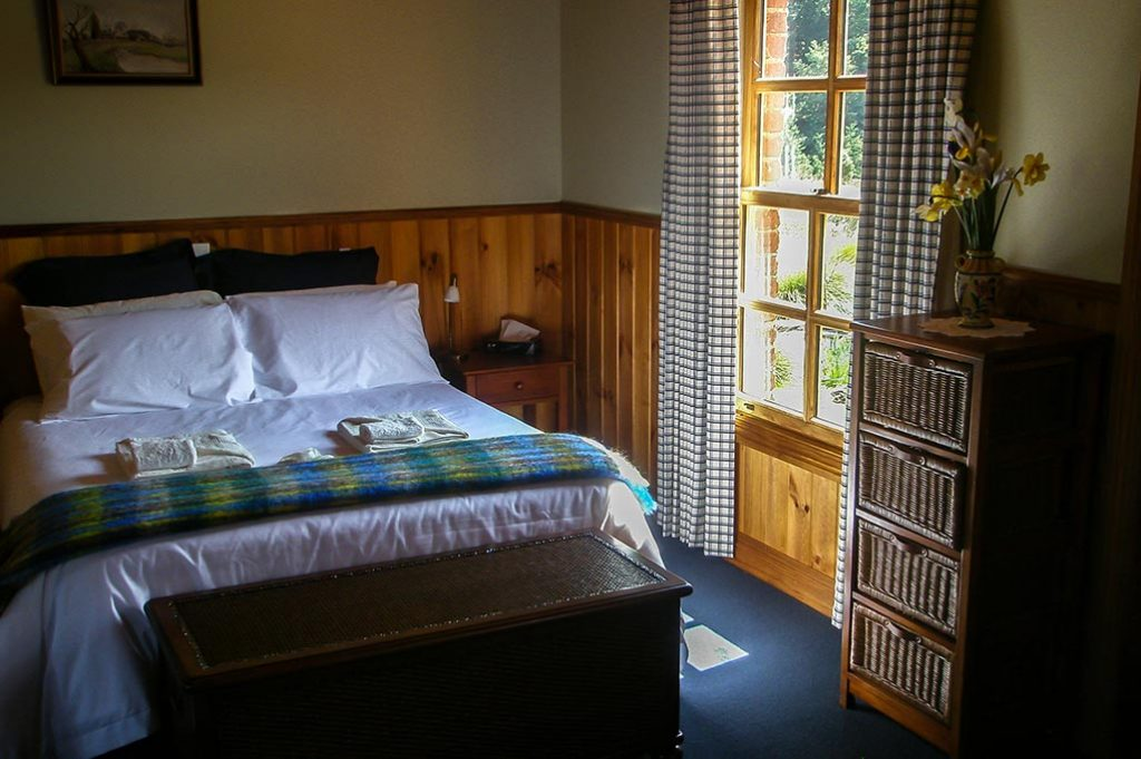 The queen bed in Fon Hock cottage is bathed in early morning sunlight.