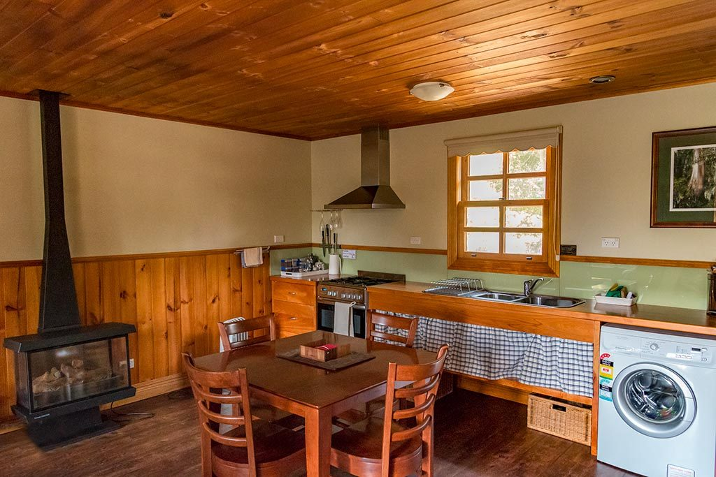 This is the dining and kitchen area in Fon Hock studio cottage, showing the stove, gas heater, kitchen bench and clothes washing machine.