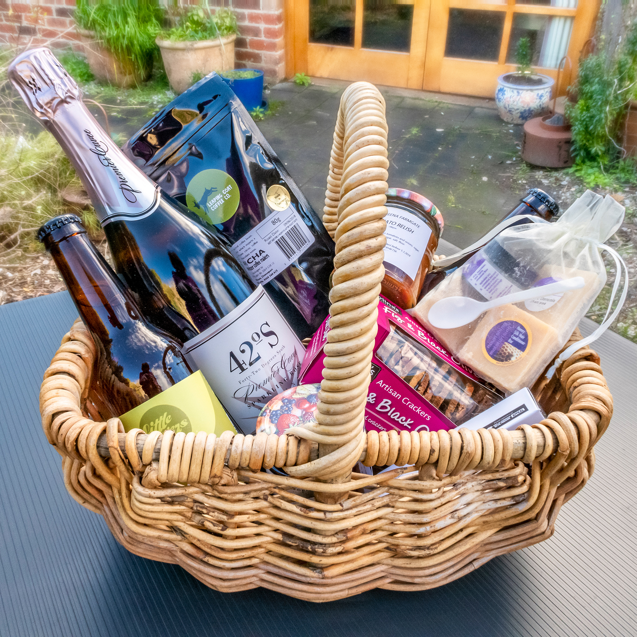 Basket containing wine, beer, ground coffee, snack foods and a small bag of spa toiletries.