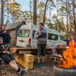 Mountain bike riders enjoying a BBQ and fire post outside the Settlers Hut: Blue Derby budget accommodation