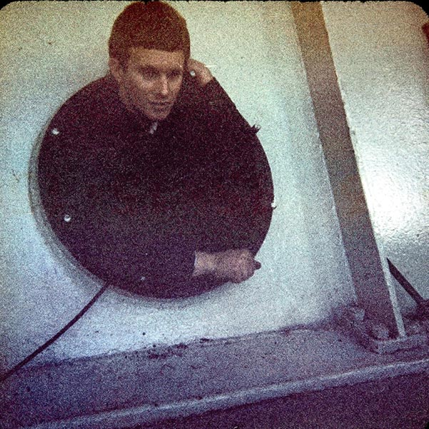 Graham ages 18 emerging from inside a large hydro turbine inspection bay.