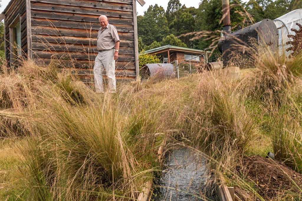 70 year-old Ron with the micro-hydro shed behind him and the hydro tail race in front of him