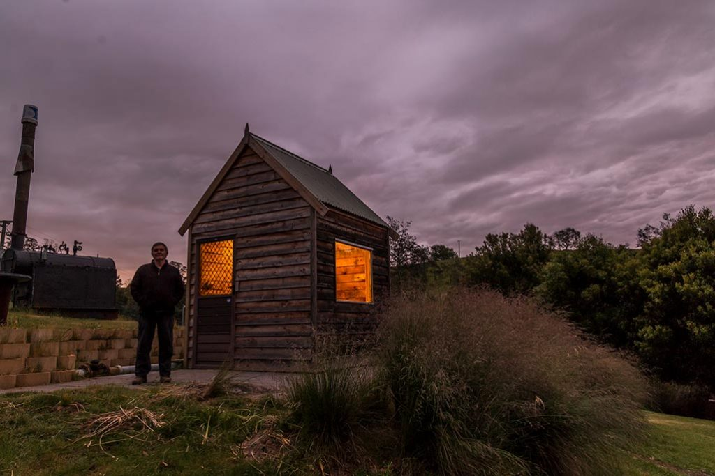 Graham stands in front of the micro hydro generator shed in the dark of evening. The light shines out of the shed.