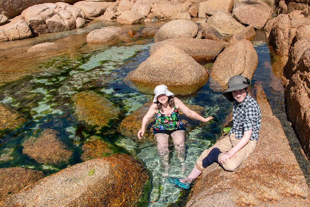 Woman in a hat and swim suit sitting in a beach rock pool with a boy sitting on a nearby rock