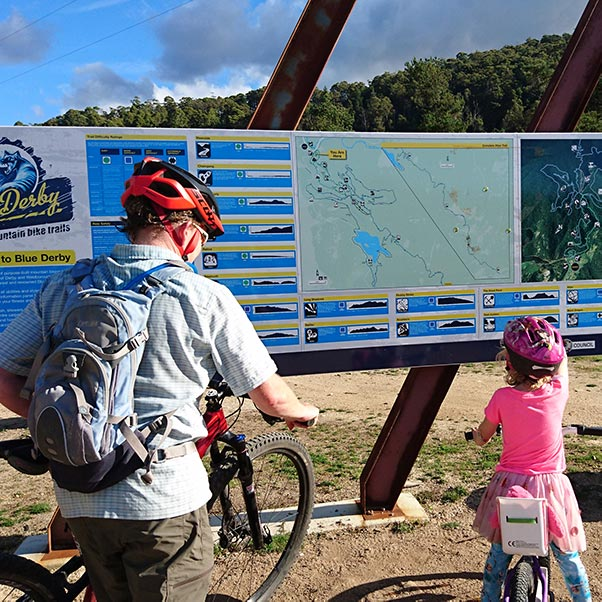 A mother and young daughter with their bikes reading the Trail Head sign at the Blue Derby Mountain Bike Park