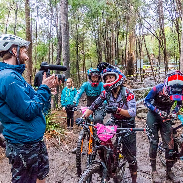Young male interviewer enjoying a moment with a female competitor during the World Enduro Series 2018