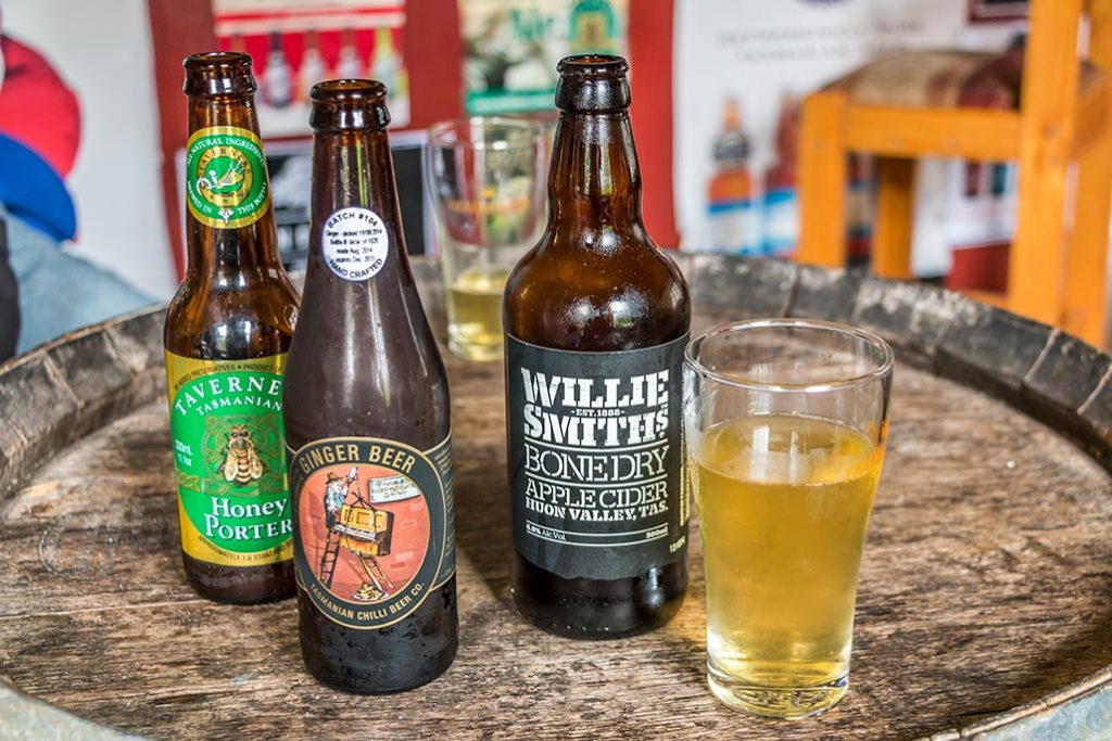 Three different bottles of craft brew and a full glass of cold cider