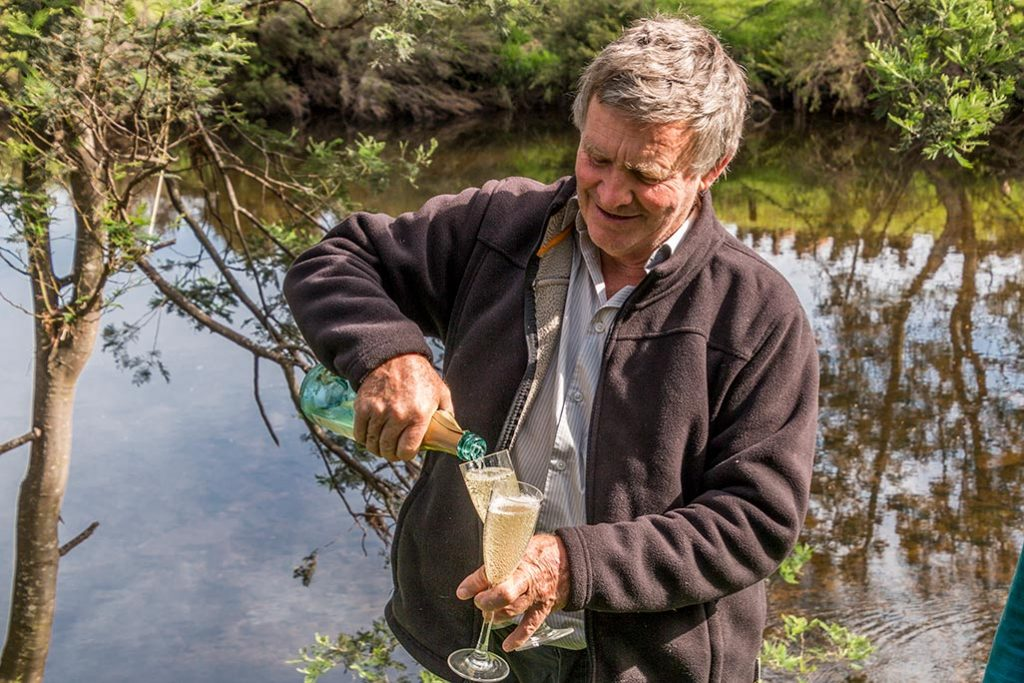 Graham pouring sparkling wine into two glasses, with the river in the background