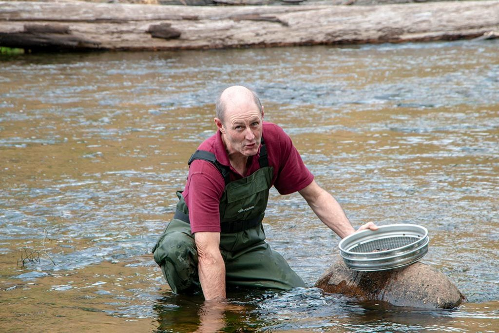 Man dressed in waders fossicking for gemstones in a Tasmanian river