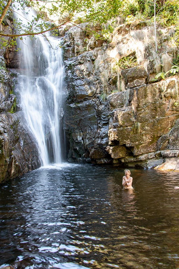 Woman with no clothes in a deep rock pool below a water fall