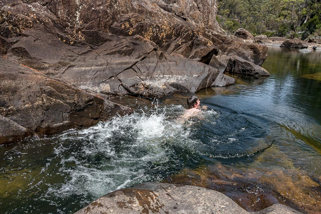 Young boy swimming in a deep rock pool making big kicking splash