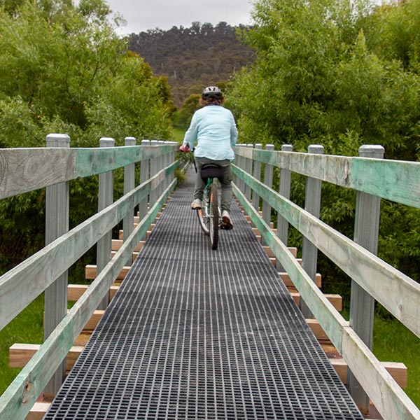A women riding a bicycle over a rail trail bridge