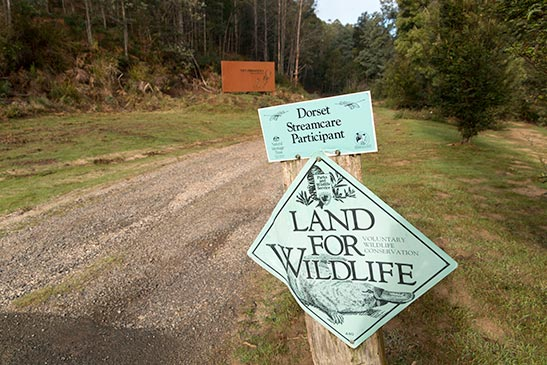 Land for Wildlife and Stream-Care signs at the entrance to Tin Dragon Cottages