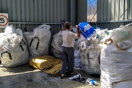 Graham placing a large bag of flexible plastic into recycling area of the Launceston rubbish centre, Tasmania