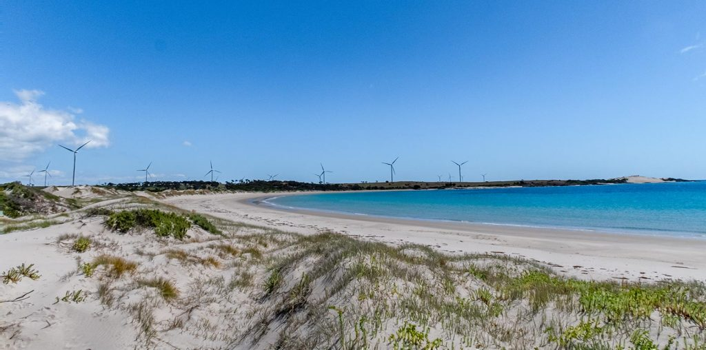 The wind turbines dominate the skyline beyond the sweeping beach of Little Musselroe Bay in North East Tasmania