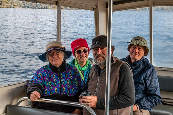 Two couples sitting the ferry boat, crossing Lake St Clair in the Cradle Mountain National park, Tasmania