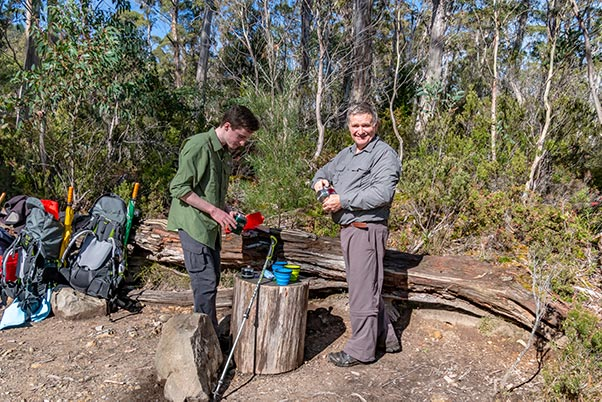 James and Graham making a cup of tea on a tree stump at the intersectin of the overland and Pine Valley tracks, Tasmania