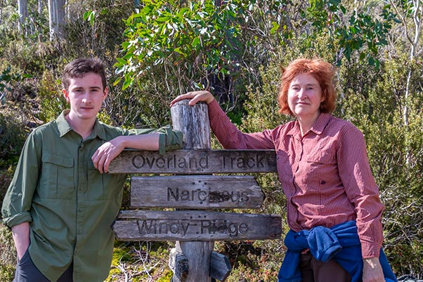 James and Christine leaning on the signposts for overland Track, Narcissus, Pine Valley Hut and Windy Ridge, Tasmania