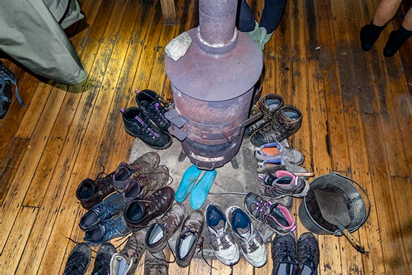 Shoes drying around the coal fire in the Lake Vera Hut