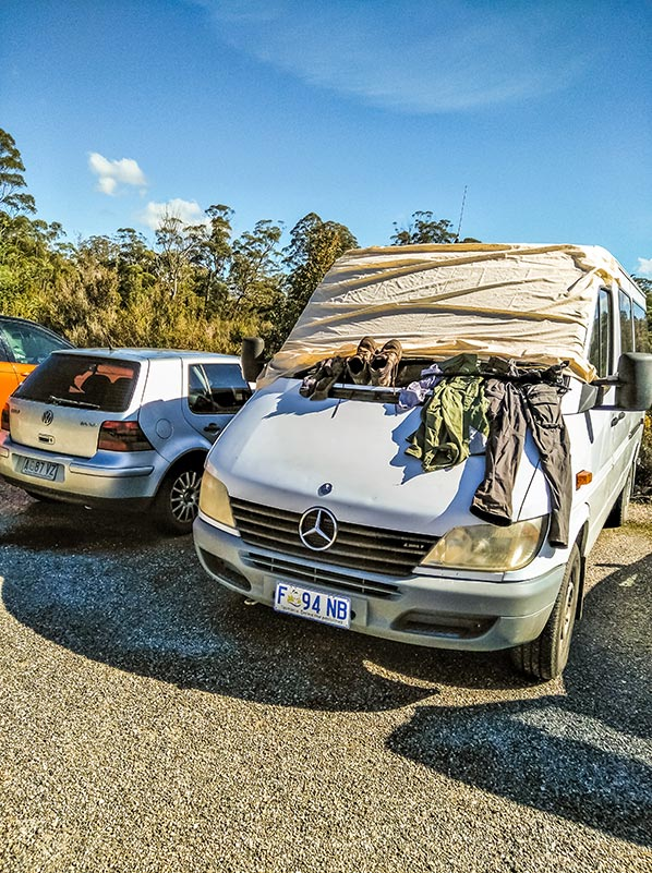 Our campervan with James's wet clothes and boots hanging from the windscreen in the Frenchmans Cap car park.