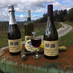 Three bottles of wine with countryside background
