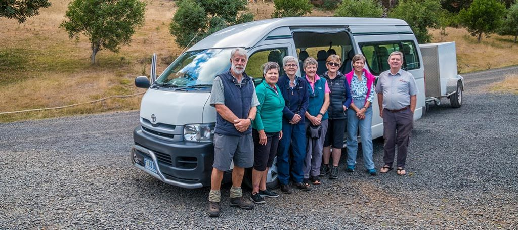 Tour group from International park tours standing in front of their mini bus at Tin Dragon Cottages