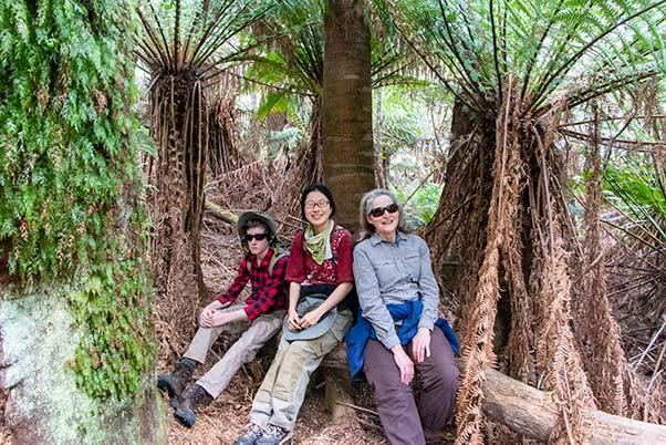 James, Shizuka and Christine taking a short break, sitting on a log