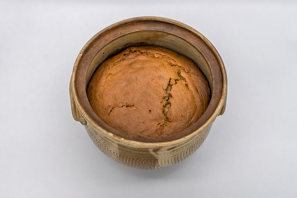 hand-made ceramic cooking pot containing freshly-baked golden-coloured apple pudding