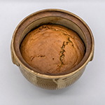 Hand-made ceramic pot containing baked apple pudding