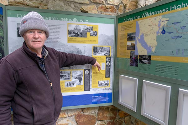 Graham pointing to a photo on the information board at the entrance to the Nelsons Falls short walk