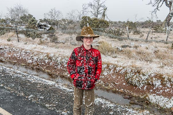 James standing on the side of the road with snow falling in the Tasmanian highlands