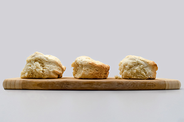 Three scones sitting on a wooden board.