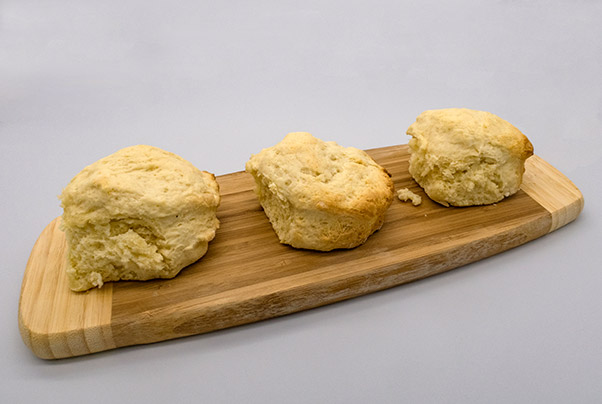 Three scones sitting on a wooden board