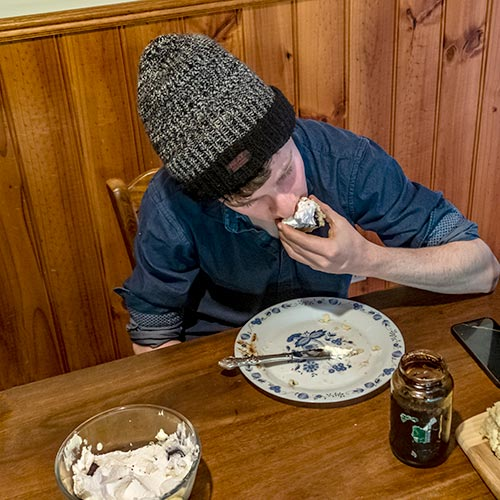 James eating a cream-covered scone at the kitchen table.