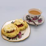 A cup of tea and a plate with scones jam and cream