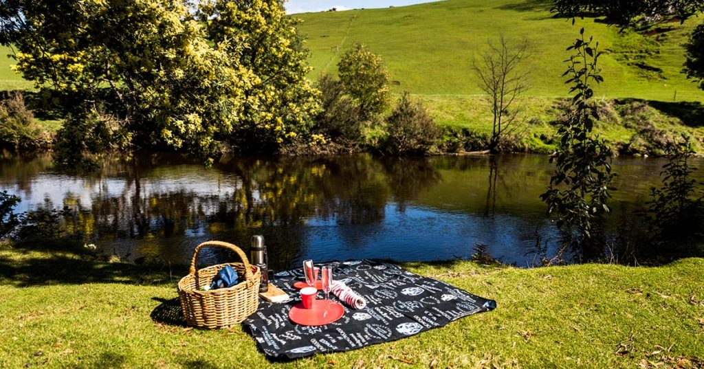 Fine food picnic basket hamper and blanket on the bank of the Ringaroooma River at Tin Dragon Cottages