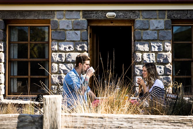 Young couple enjoying breakfast in front of Ah back studio spa cottage near Derby in Tasmania
