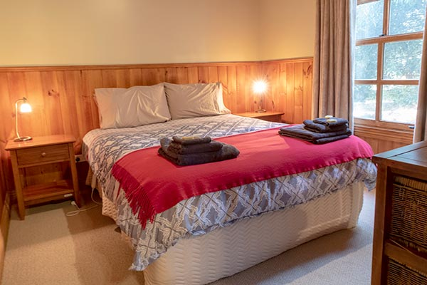 Queen-size bed in the first bedroom of Ah Moy self-contained cottage is wheelchair accessible.