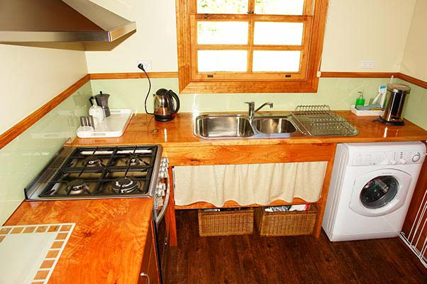 Kitchen in Ah Moy cottage showing the gas-top stove, electric oven, sink and washing machine.