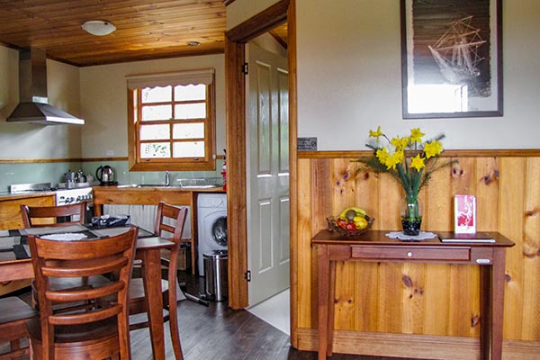 Interior of Ah Ping cottage shows the kitchen, dining area and door leading to the bathroom.