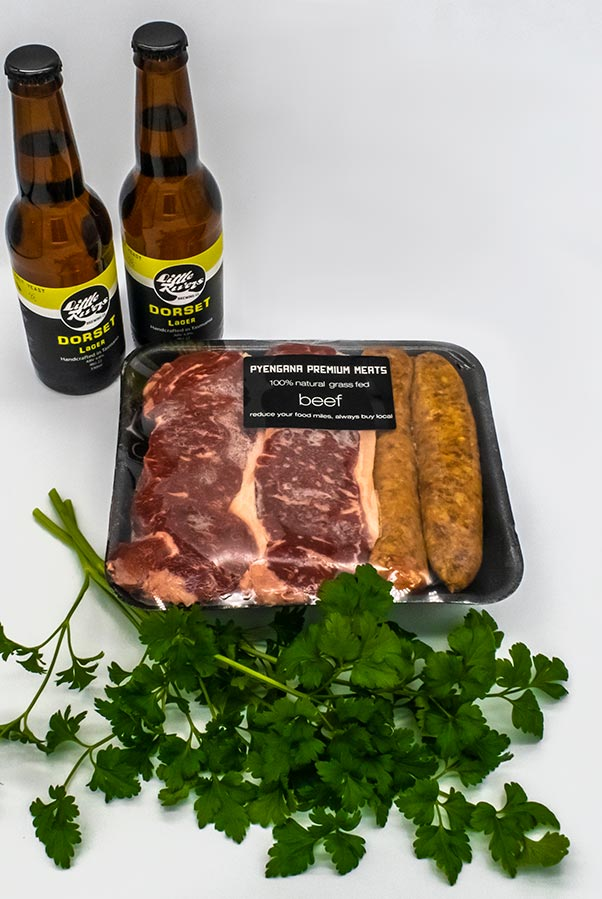 Two bottles of Little Rivers beer and a tray of porterhouse steak and sausages.