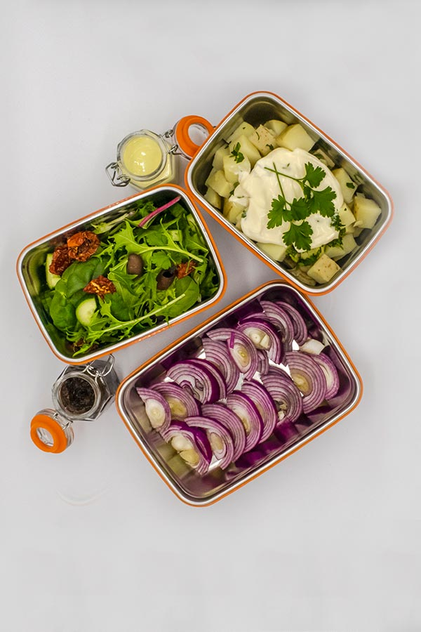 Three trays containing fresh salads and two bottles of chutney and salad dressing.