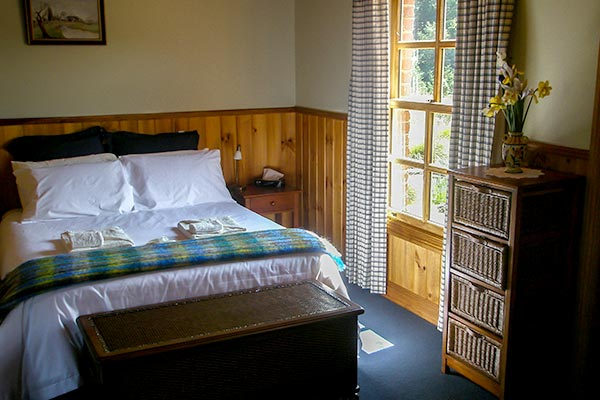 Queen bed with slight streaming in the window in Fon Hock cottage accommodation near Derby in Tasmania