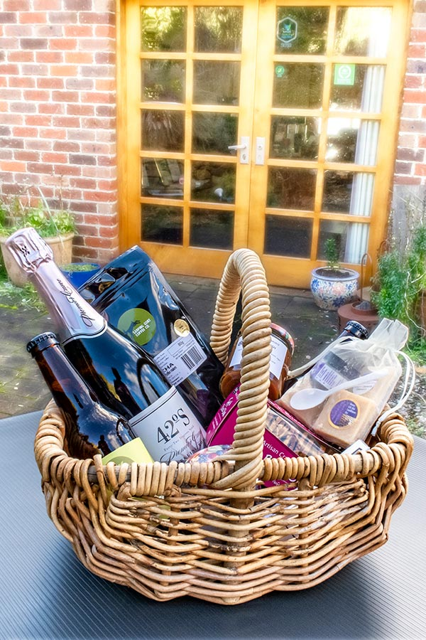 A food hamper of sparkling wine, cheese, biscuits, fudge, chutney, ground coffee and other fine foods. in a cane basket.