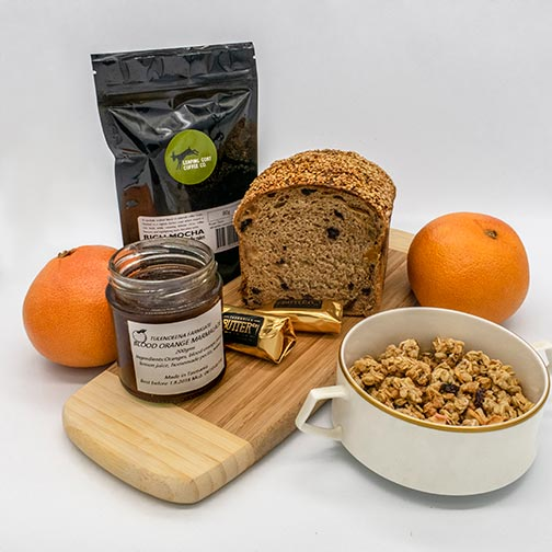 Breakfast foods including jam, bread, butter, muesli and oranges