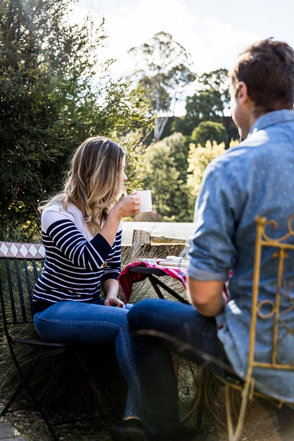 Woman and man sitting at an outside table drinking coffee