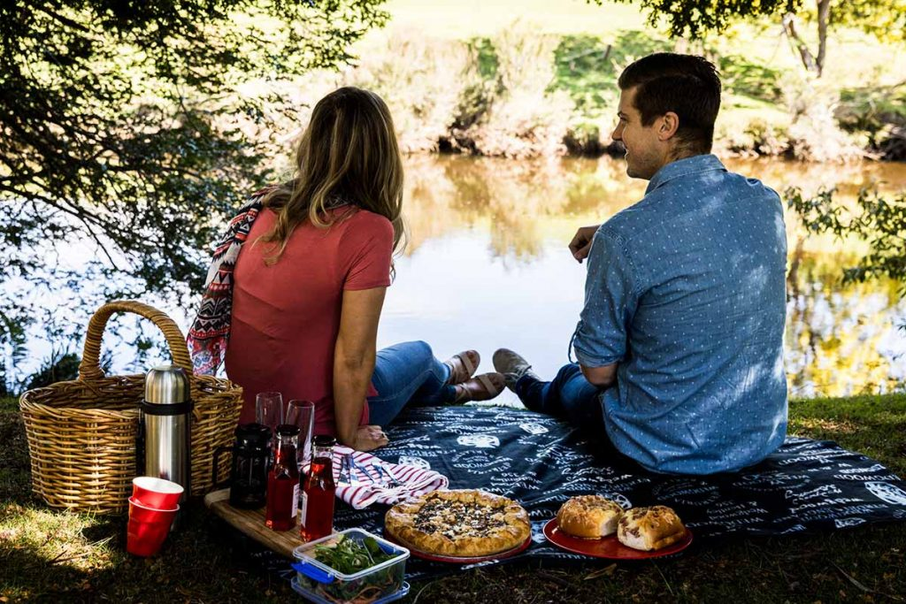 A woman and man sitting on the river bank, with a picnic food hamper.