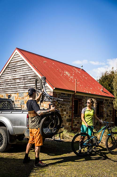 Man and woman retrieving their mountain bikes from the back of their car.